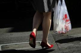 A woman carries a plastic bag in Chinatown in San Francisco, Calif., Monday, October 1, 2012.  San Francisco's city-wide plastic bag ban went into effect Monday, and now people will be charged ten cents for paper bags.