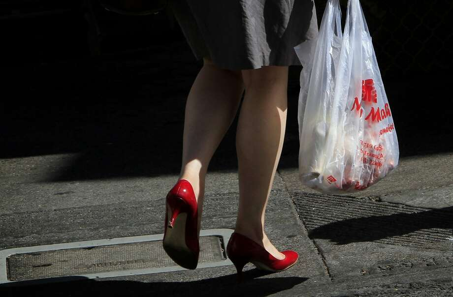 A woman carries a plastic bag in Chinatown in San Francisco, Calif., Monday, October 1, 2012.  San Francisco's city-wide plastic bag ban went into effect Monday, and now people will be charged ten cents for paper bags. Photo: Sarah Rice, Special To The Chronicle