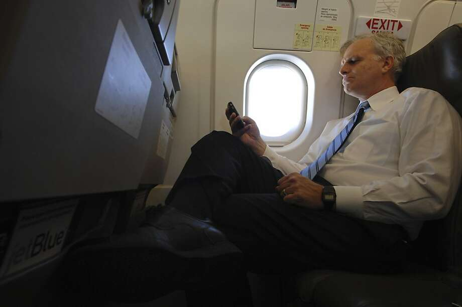 David Neeleman, founder and chairman of JetBlue Airways, tests a then-new in-flight Wi-Fi connection in 2007. Photo: Robert Stolarik, NYT