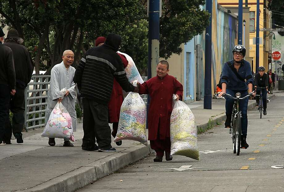 Buddhist monks haul aluminum cans and confetti to the recycling center at Church and Market streets. Photo: Liz Hafalia, The Chronicle