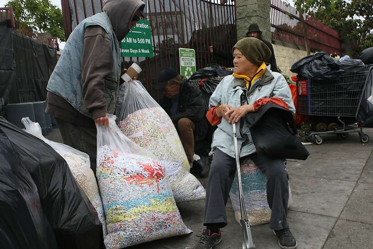Site worker Brian McMahon (left) recycles paper confetti at the recycling center at Church on Market streets in San Francisco, Calif., as people wait for the center to open on Friday, August 9, 2013. Safeway is going to shut down its recycling center here by September 6.