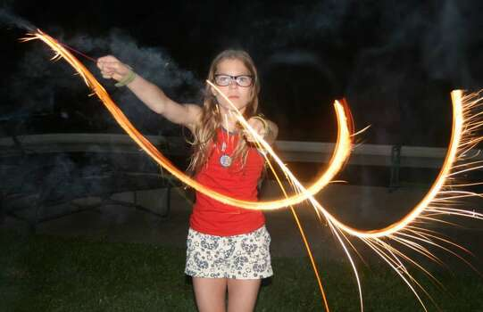 This was taken on the Fourth of July, in greater Chicagoland. This is my daughter, Gina, armed with a sparkler. My family traditionally gets together over the Fourth and a good time is had by all. We grill dinner and enjoy the company of family. And play (safely!) with sparklers.