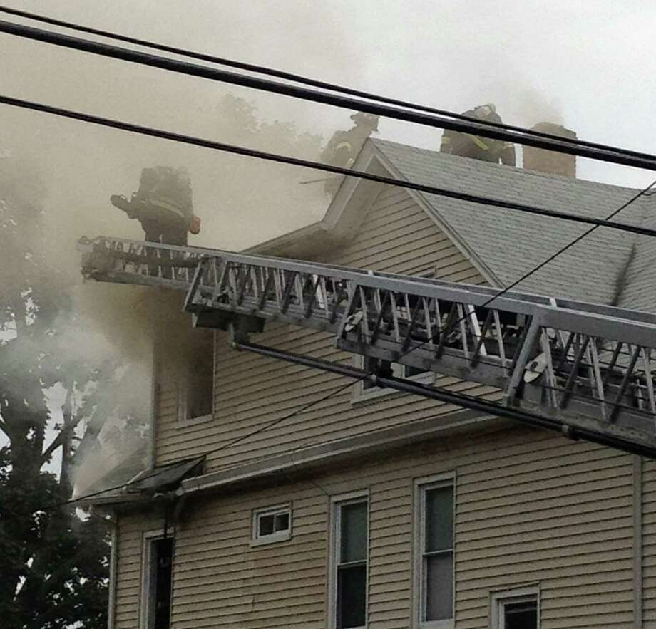 City fire crews responded to the three-unit building at 188-192 Monroe St. at about 5 p.m. on reports of smoke and flames curling out of the third floor eaves. Photo: Denis O'Malley / Connecticut Post