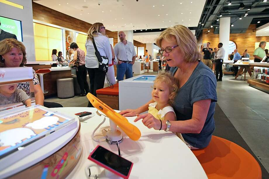 A woman and young child browse the products in an AT&T store in Chicago that isn't yet made over. Photo: Tim Boyle, Bloomberg