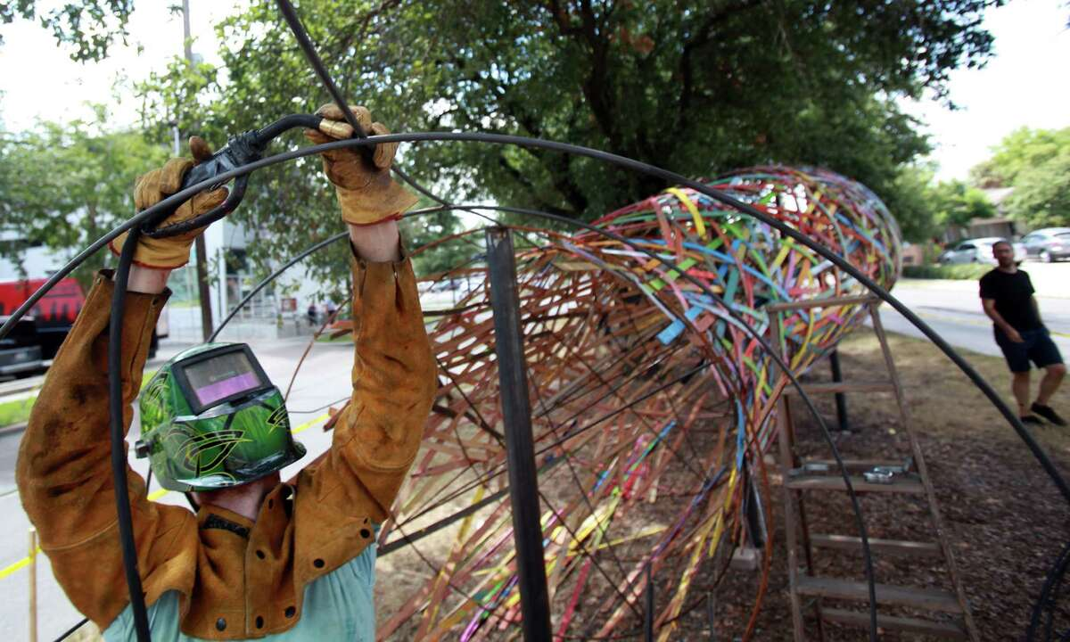 """Artist Patrick Renner builds the metal frame of the 'Funnel Tunnel' to connect the missing section on Monday, Aug. 5, 2013, in Houston. The """"Funnel Tunnel"""" is a public art project intended to increase the cultural, social, and economic value of the Montrose area, according to the Art League Houston. The Dedication Ceremony is Saturday, August 10 from 6 - 9p.m. at Inversion Coffee parking lot."""