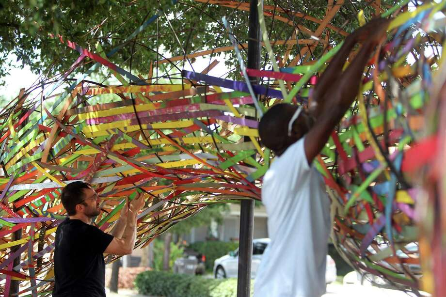 Garrett Arnold and photographer Ronald Jones help Artist Patrick Renner as he assembles the 'Funnel Tunnel' on Monday, Aug. 5, 2013, in Houston. Photo: Mayra Beltran, Houston Chronicle / © 2013 Houston Chronicle
