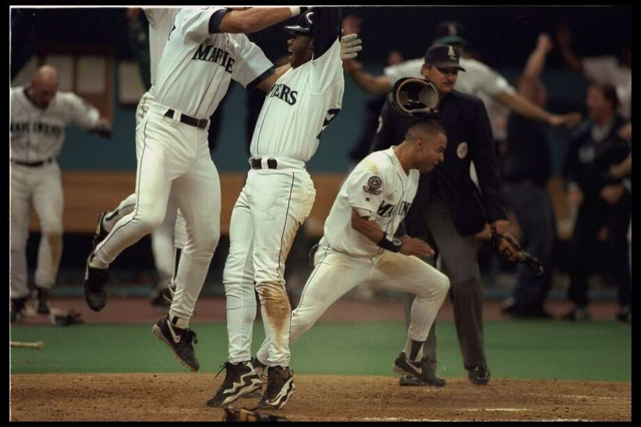 Griffey, center, jumps with joy after scoring the winning run. The M's beat the Yankees 6-5 in 11 innings to advance to the A.L. Championship Series.