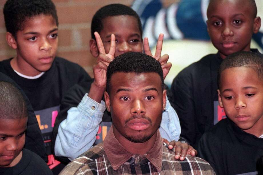 Ten-year-old Morris Richardson gives an unwitting Ken Griffey Jr. bunny ears during a photo session at a Boys and Girls Club event in December 1996 in Seattle.