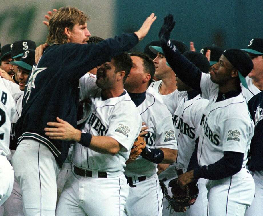 Griffey, right, shares a high-five with Mariners ace Randy Johnson as the team celebrates clinching the A.L. West title Sept. 23, 1997, in Seattle.