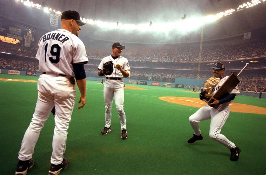 The Kid playfully struggles with his Gold Glove and Silver Slugger awards as Jay Buhner and David Segui watch, before the start of the Mariners' Opening Day game April 5, 1999, at the Kingdome.  Photo: Paul Joseph Brown, Seattle P-I Archives