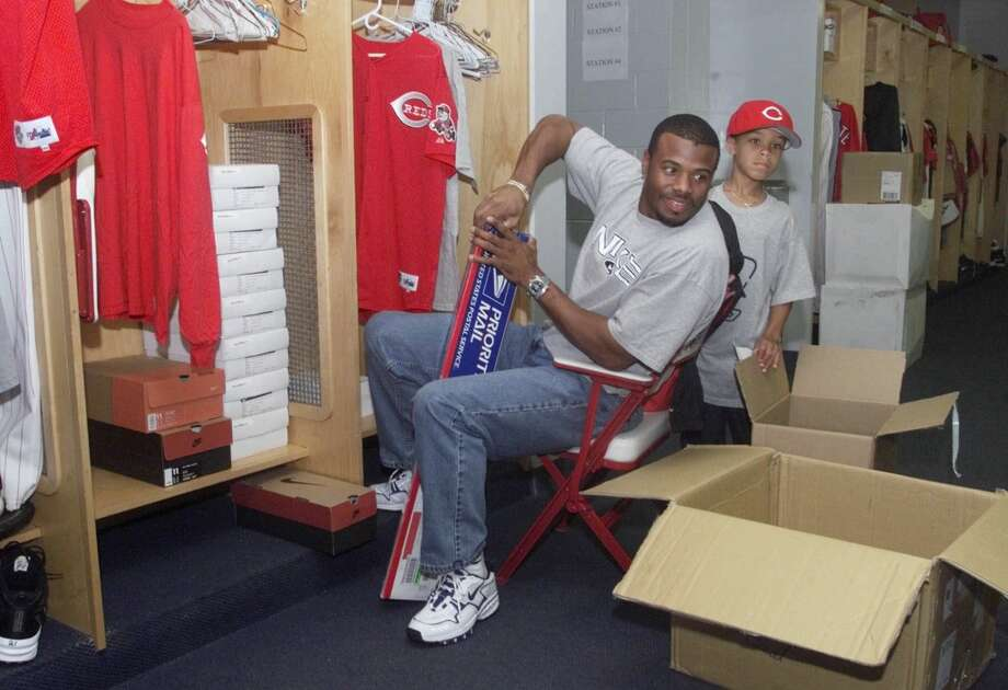 Back with his hometown Reds and reunited with his father, who was a coach for Cincinnati, Griffey here settles into his new team's spring-training clubhouse in Sarasota, Fla., on Feb. 20, 2000. With him is his son, Trey, who was 6 at the time.  Photo: Al Behrman, Associated Press