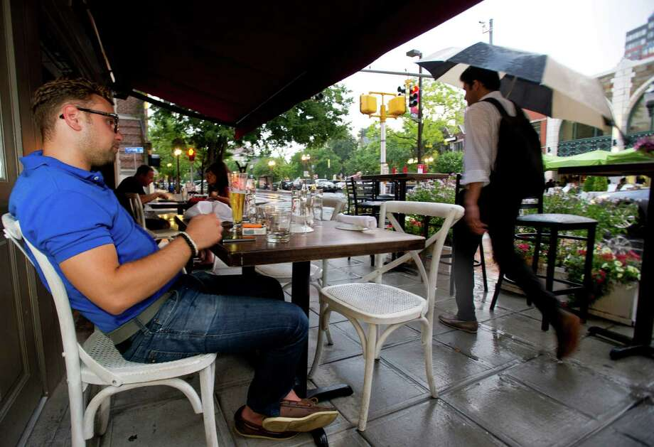 Steve Aivalis sits under an awning at a table at Barrique Bistro and Wine Bar as pedestrians with umbrellas pass by in the rain on Bedford Street on Friday, August 9, 2013. Photo: Lindsay Perry / Stamford Advocate