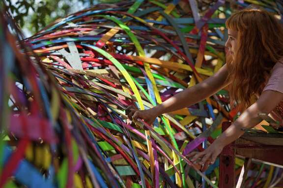 """Assistant Nadia Al-Khalifah helps install the giant art installation """"Funnel Tunnel"""" on Friday along Montrose Boulevard."""