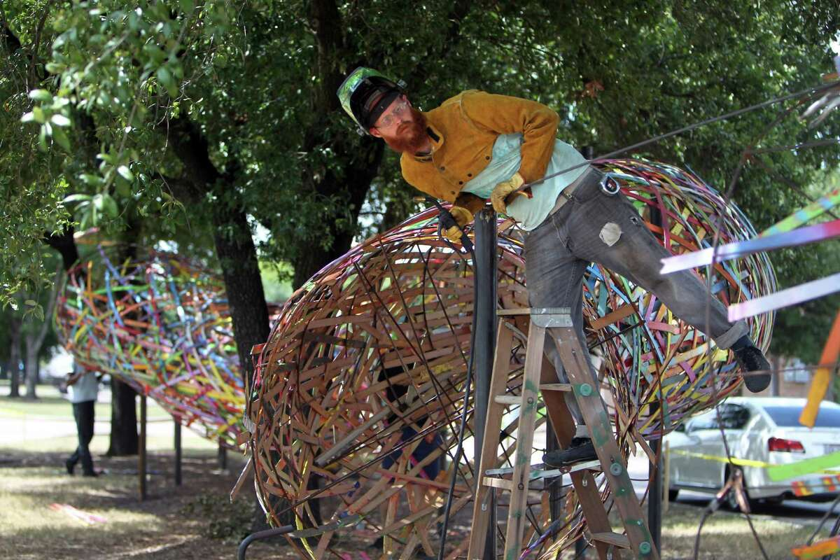 """Artist Patrick Renner, creator of the """"Funnel Tunnel,"""" works on the metal frame of the piece on Monday. """"It's about energy being funneled to a point,"""" Renner says."""