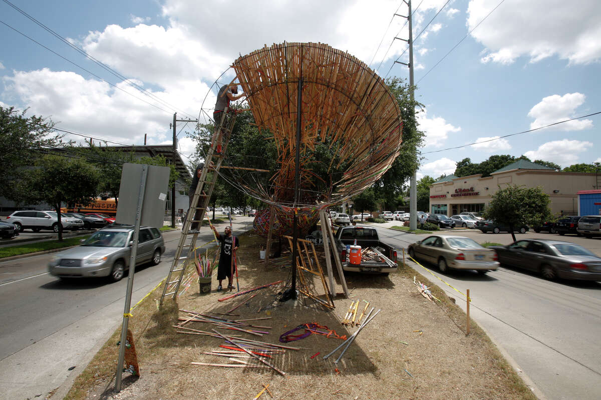 """Artist Patrick Renner, center left, with the help of many assistants, installs the """"Funnel Tunnel"""" on Friday along Montrose Boulevard in Houston. This is the first installation of Art League Houston's Esplanade Project."""