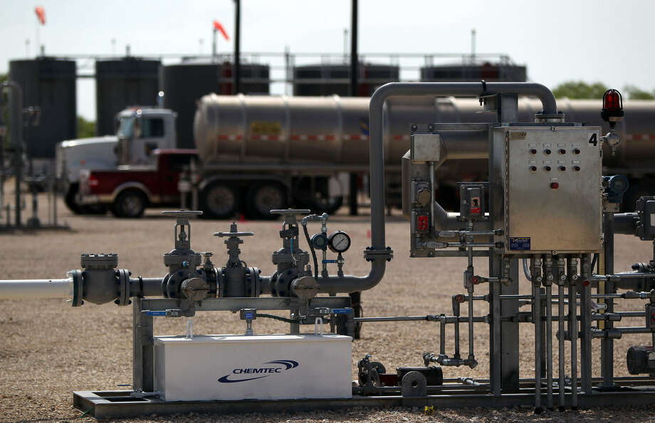 A tanker truck (background) unloads oil into storage tanks that will be refined at the Valero Three Rivers Refinery in Three Rivers. In the foreground is a custody transfer station that helps move the oil from the storage tanks (behind truck) over to the refinery. Photo: Express-News File Photo