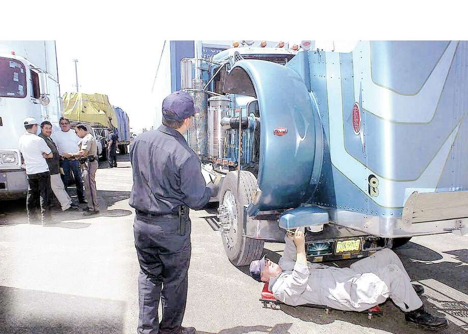 Two Department of Public Safety employees inspect a truck entering El Paso from Mexico. El Paso is one of the five entities picked for a five-year pilot program allowing them to reimburse the Homeland Security Department for more customs staffing.