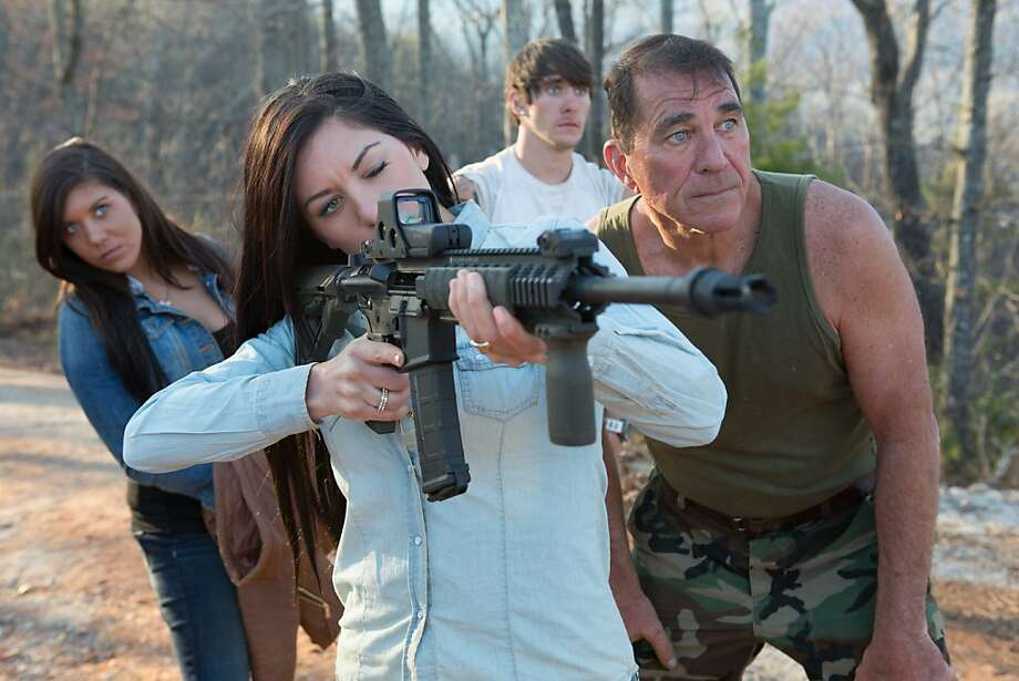 "Ashley aims a paintball gun as Lindsey, Michael and Brent Sr. look on - preppers in the waiting game at ""Doomsday Castle."""