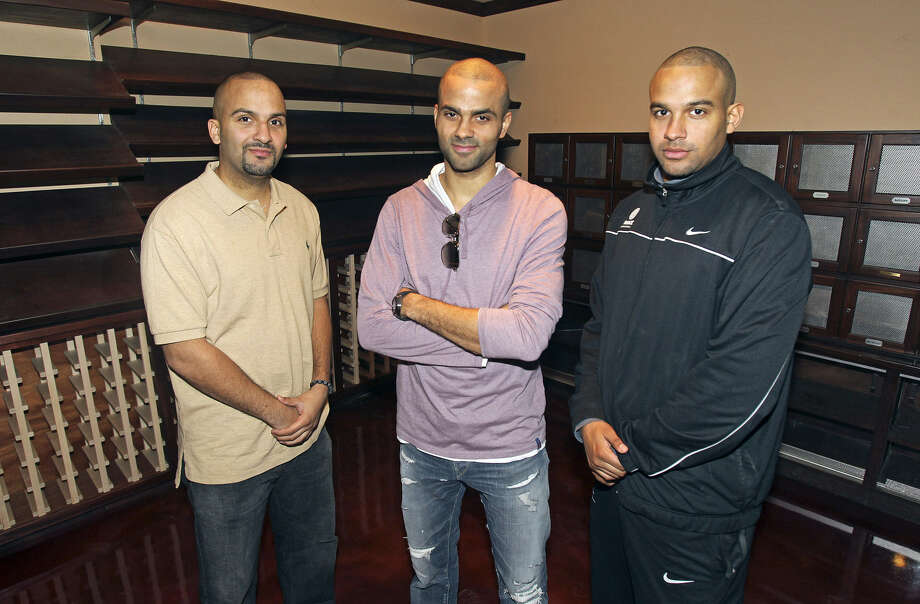 Tony Parker is flanked by brothers TJ (left) and Pierre in a wine and cigar room at Nueve Lounge when it opened in February 2012. The nightclub closed on July 27. Photo: Express-News File Photo
