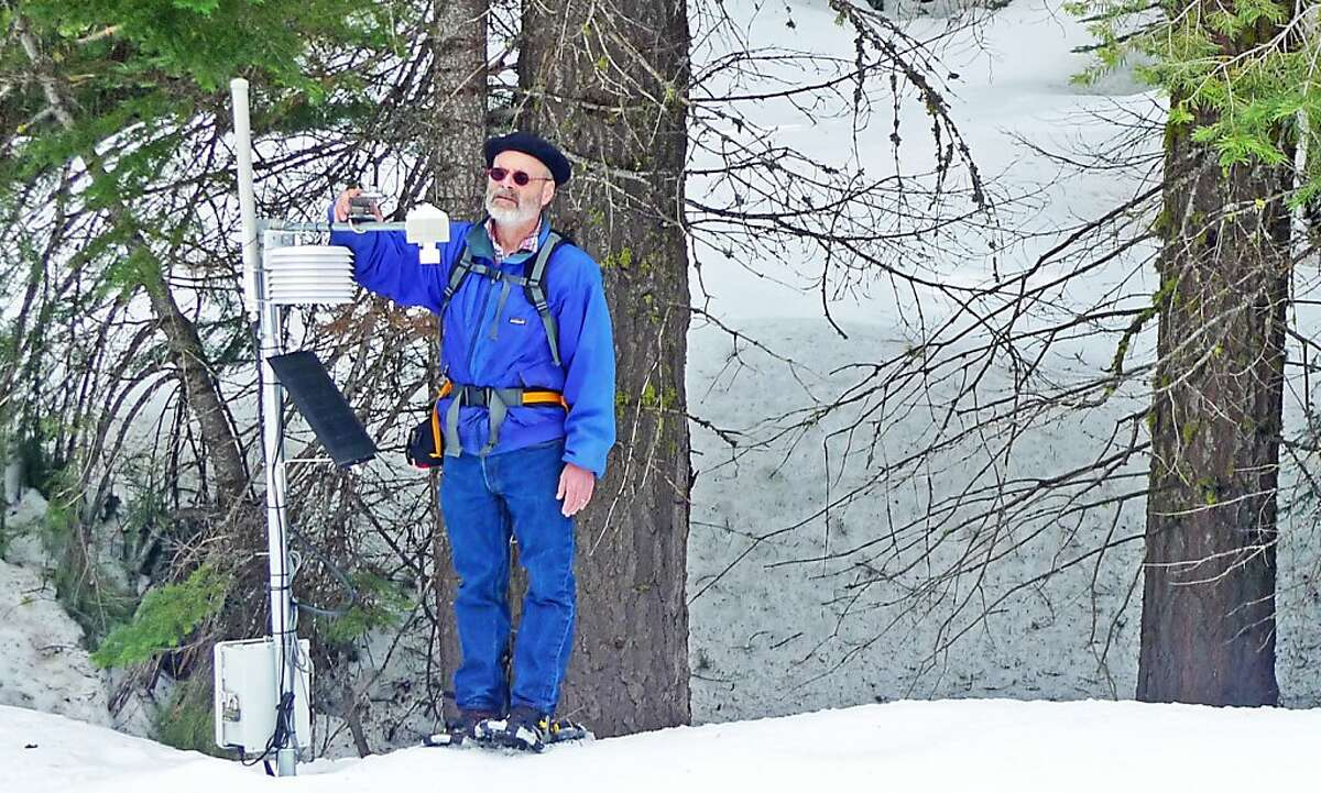 Steven Glaser adjusting the solar radiation sensor at a wireless sensor network station. Visible is the snow depth sensor at the end of the cross-ark and the housing for the temperature - relative humidity sensor. The radio and electronics are in the box bolted to the pole.