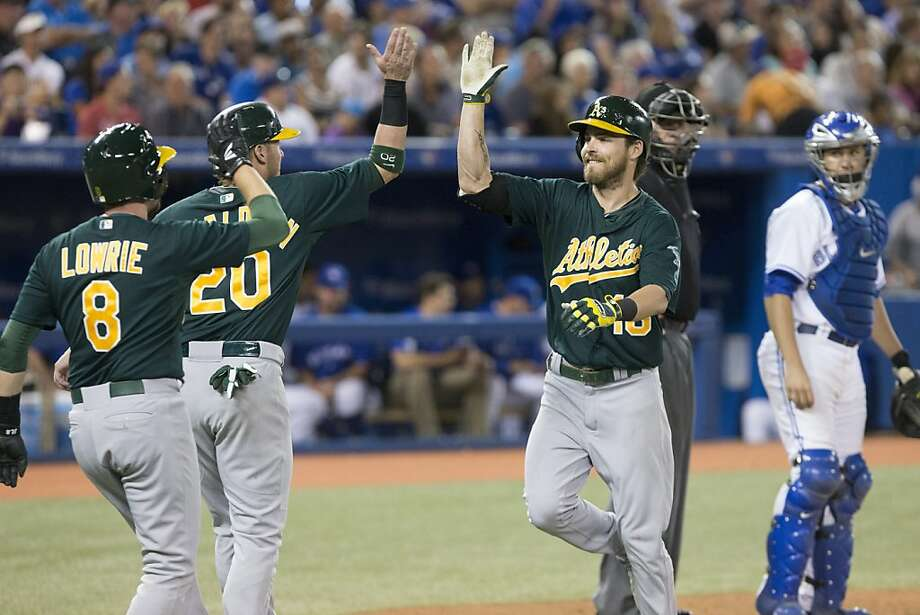 Oakland Athletics' Josh Reddick, right, front, celebrates at the plate with Josh Donaldson and Jed Lowrie, left, after hitting a three-run home run as Toronto Blue Jays catcher Josh Thole watches during the sixth inning of a baseball game in Toronto on Friday, Aug. 9, 2013. (AP Photo/The Canadian Press, Chris Young) Photo: Chris Young, Associated Press