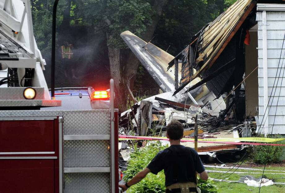 A pilot and his son in the midst of touring college campuses crashed into a Connecticut house, and as many as six people are feared dead — three in the house and three on the ground. Photo: Fred Beckham / Associated Press