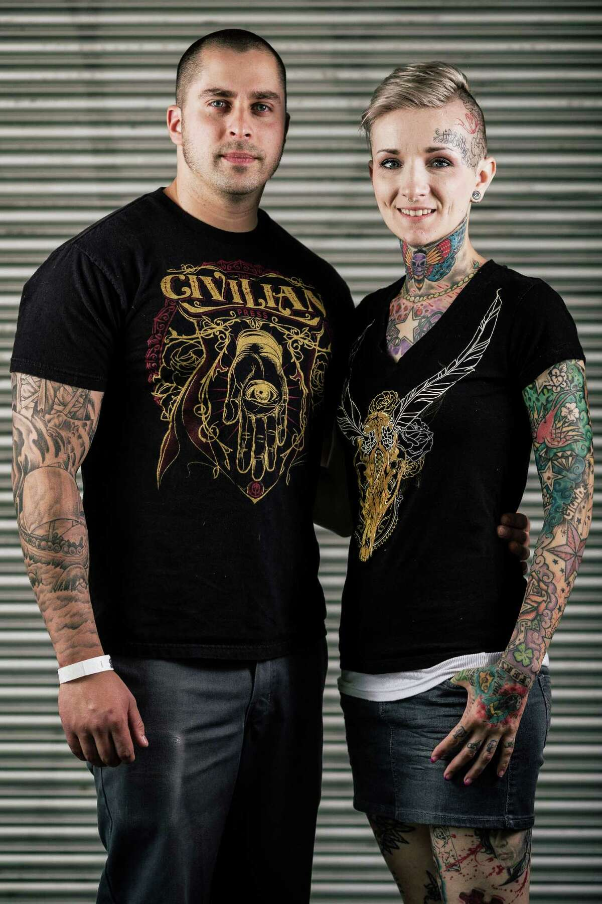 Sal Rico-Martin, left, and Amanda Midland, right, show off their ink during the first of three days of the Seattle Tattoo Expo Friday, August 9, 2013, at the Seattle Center in Seattle.