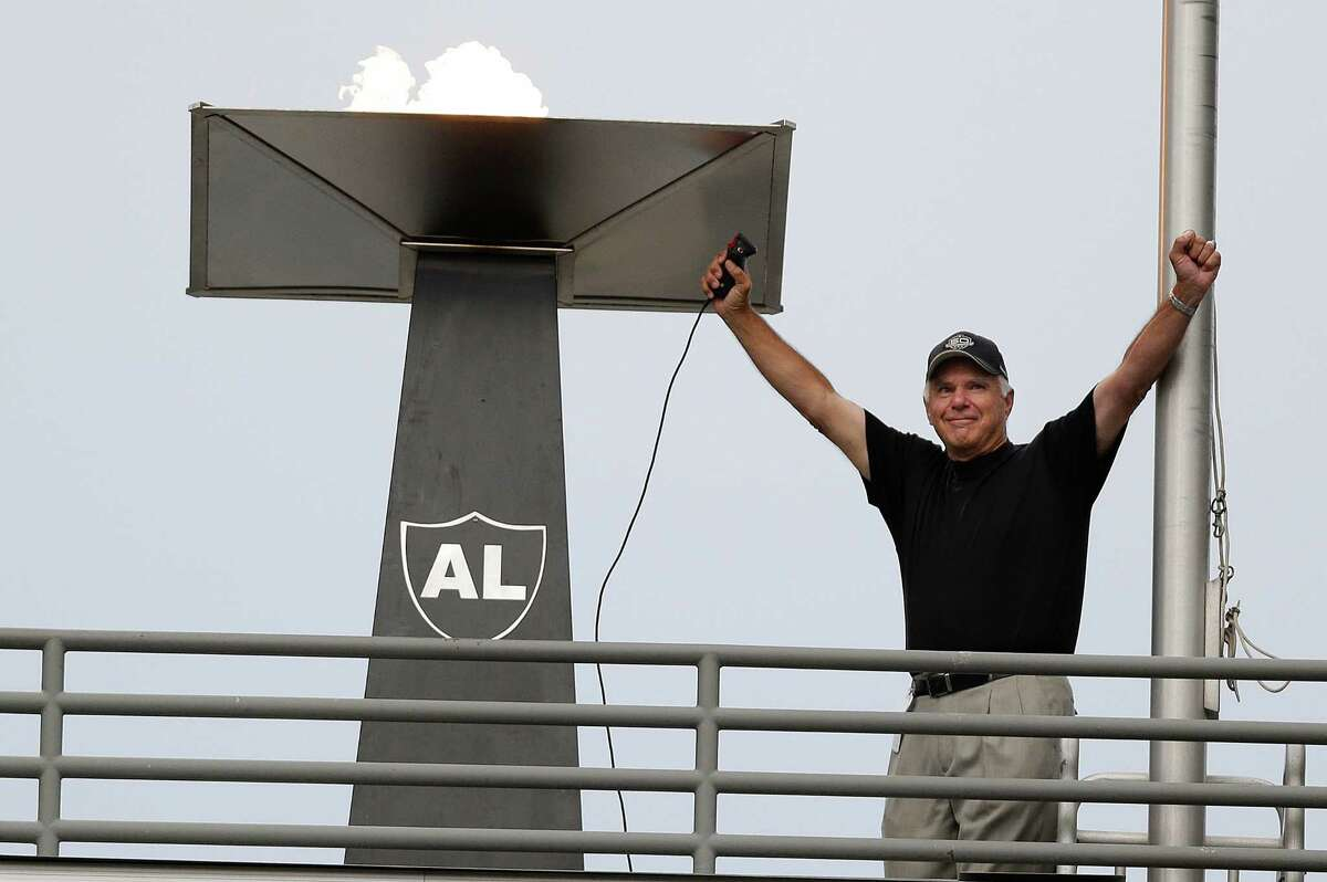 Former Oakland Raiders quarterback Daryle Lamonica raises his arms after lighting a torch for former owner Al Davis before an NFL preseason football game between the Oakland Raiders and the Dallas Cowboys in Oakland, Calif., Friday, Aug. 9, 2013. (AP Photo/Marcio Jose Sanchez)