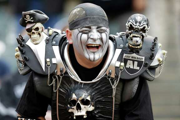 An Oakland Raiders fan smiles during an NFL preseason football game between the Oakland Raiders and the Dallas Cowboys in Oakland, Calif., Friday, Aug. 9, 2013. (AP Photo/Ben Margot)