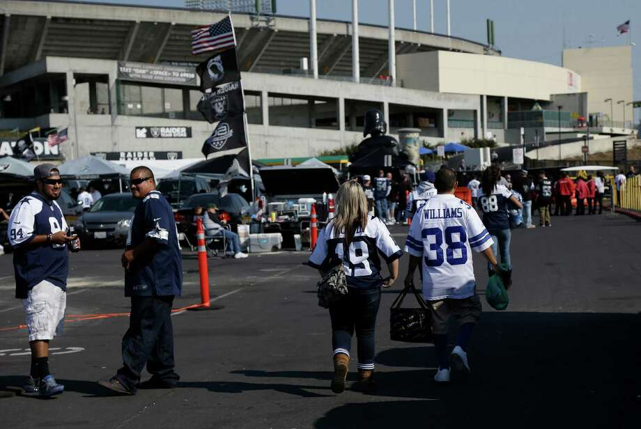 Dallas Cowboys fans walk toward O.co Coliseum before an NFL preseason football game between the Oakland Raiders and the Dallas Cowboys in Oakland, Calif., Friday, Aug. 9, 2013. (AP Photo/Marcio Jose Sanchez) Photo: Marcio Jose Sanchez, Associated Press / AP