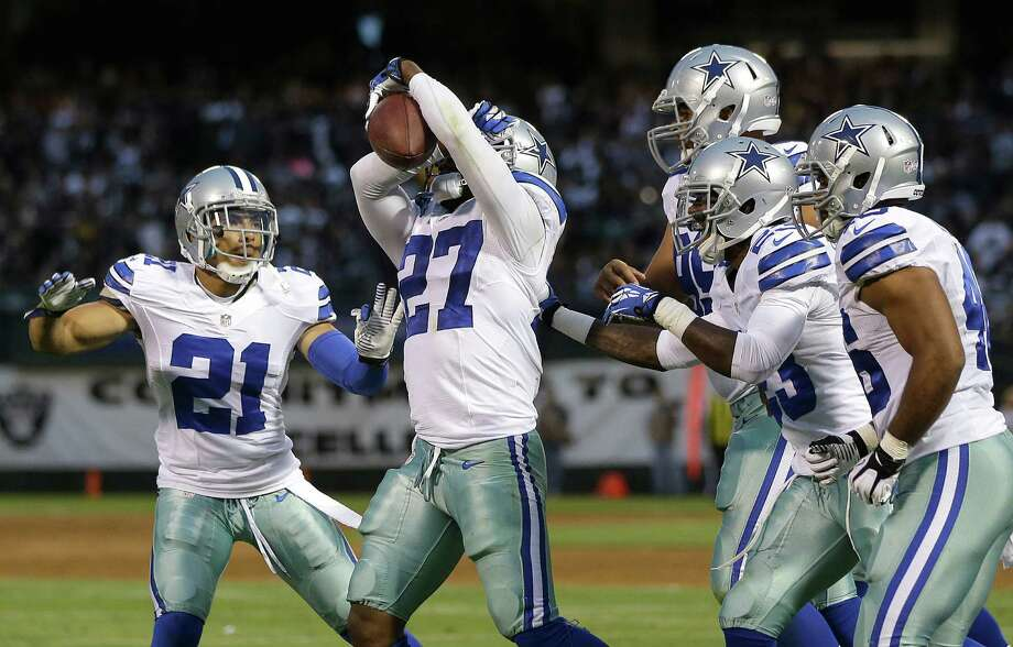 Dallas Cowboys defensive back J.J. Wilcox (27) celebrates with cornerback Sterling Moore (21) and teammates after intercepting a pass from Oakland Raiders quarterback Terrelle Pryor during the second quarter of an NFL preseason football game in Oakland, Calif., Friday, Aug. 9, 2013. (AP Photo/Marcio Jose Sanchez) Photo: Marcio Jose Sanchez, Associated Press / AP