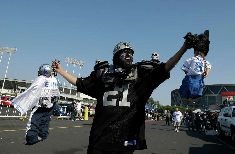 Oakland Raiders fan Julio Caballero holds up dolls of the Dallas Cowboys before an NFL preseason football game between the Oakland Raiders and the Dallas Cowboys in Oakland, Calif., Friday, Aug. 9, 2013. (AP Photo/Marcio Jose Sanchez) Photo: Marcio Jose Sanchez, Associated Press / AP