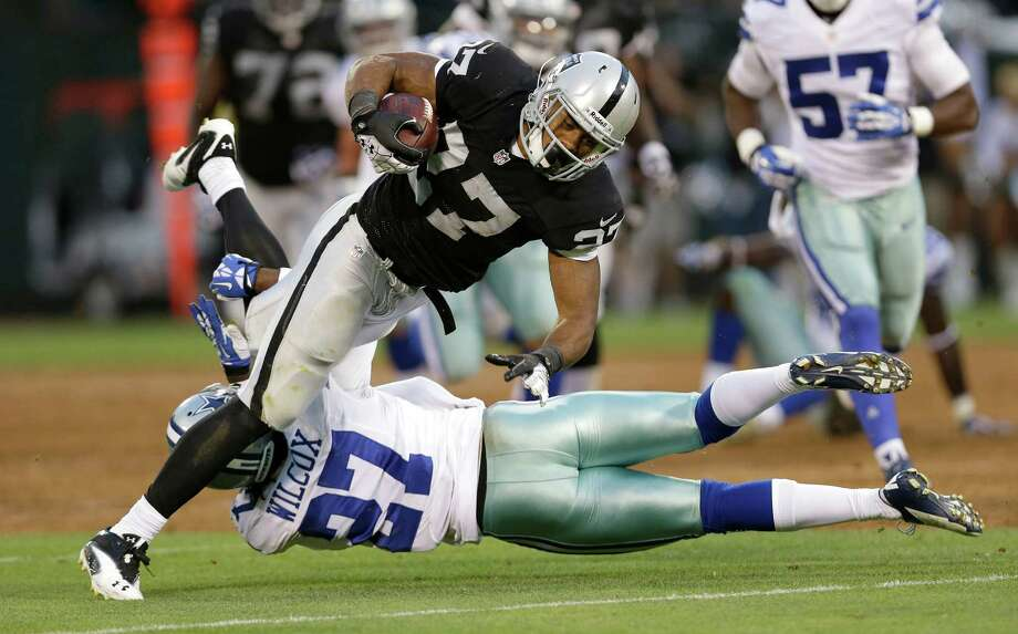 Oakland Raiders running back Rashad Jennings carries against Dallas Cowboys defensive back J.J. Wilcox, bottom, during the second quarter of an NFL preseason football game in Oakland, Calif., Friday, Aug. 9, 2013. (AP Photo/Marcio Jose Sanchez) Photo: Marcio Jose Sanchez, Associated Press / AP