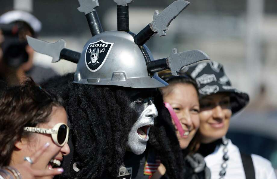 "Oakland Raiders fan ""Dr. Death"" Ray Perez, center, poses for photographs with fans before an NFL preseason football game between the Oakland Raiders and the Dallas Cowboys in Oakland, Calif., Friday, Aug. 9, 2013. (AP Photo/Ben Margot) Photo: Ben Margot, Associated Press / AP"