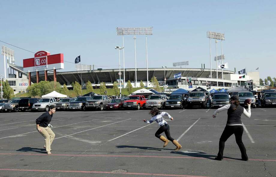 Fans play football in the O.co Coliseum parking lot before an NFL preseason football game between the Oakland Raiders and the Dallas Cowboys in Oakland, Calif., Friday, Aug. 9, 2013. (AP Photo/Marcio Jose Sanchez) Photo: Marcio Jose Sanchez, Associated Press / AP
