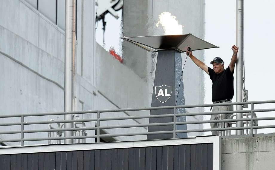 Former Oakland Raiders quarterback Daryle Lamonica raises his arms after lighting a torch for former owner Al Davis before an NFL preseason football game between the Oakland Raiders and the Dallas Cowboys in Oakland, Calif., Friday, Aug. 9, 2013. (AP Photo/Ben Margot) Photo: Ben Margot, Associated Press / AP
