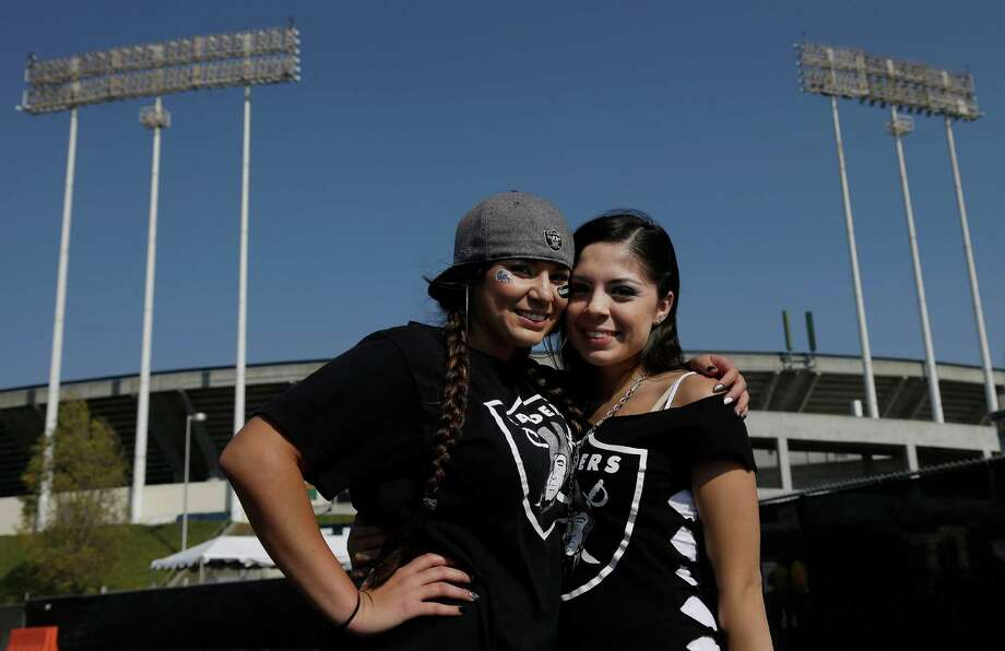 Oakland Raiders fans Elizabeth Rocha, left, and Mercedes Gonzales pose for photographs in front of O.co Coliseum before an NFL preseason football game between the Oakland Raiders and the Dallas Cowboys in Oakland, Calif., Friday, Aug. 9, 2013. (AP Photo/Marcio Jose Sanchez) Photo: Marcio Jose Sanchez, Associated Press / AP