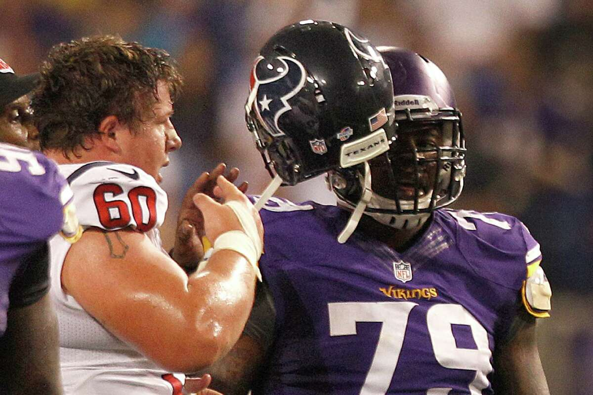 Indicative of the contact, Texans guard Ben Jones (60) tries to free his helmet from the face mask of Everett Dawkins.
