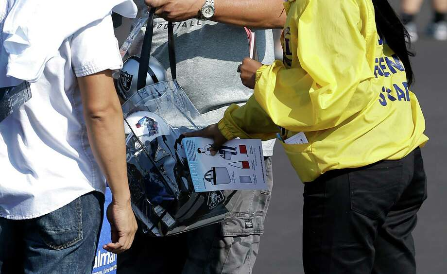 A stadium worker gives instructions to fans on bags being brought into O.co Coliseum before an NFL preseason football game between the Oakland Raiders and the Dallas Cowboys in Oakland, Calif., Friday, Aug. 9, 2013. (AP Photo/Ben Margot) Photo: Ben Margot, Associated Press / AP