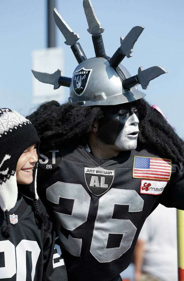 "Oakland Raiders fan ""Dr. Death"" Ray Perez poses for photographs with fans before an NFL preseason football game between the Oakland Raiders and the Dallas Cowboys in Oakland, Calif., Friday, Aug. 9, 2013. (AP Photo/Ben Margot) Photo: Ben Margot, Associated Press / AP"