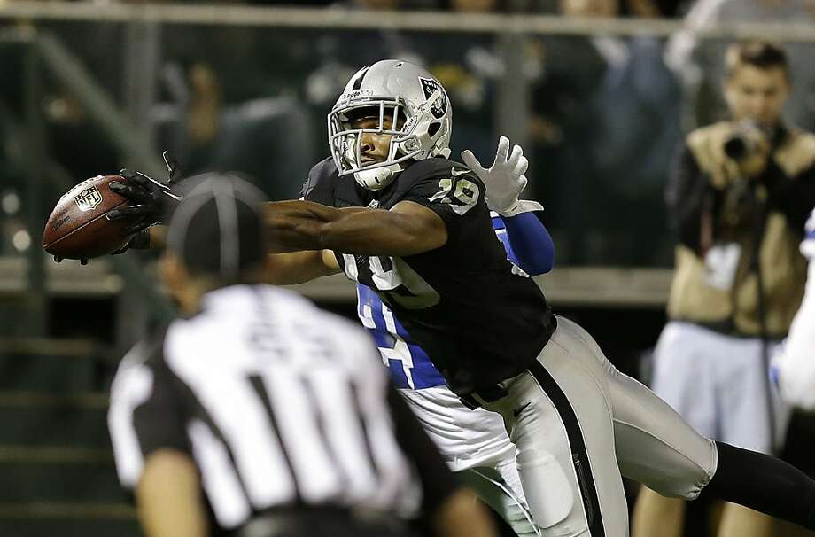 Rookie wide receiver Brice Butler hauls in a 30-yard touchdown pass from Matt McGloin in the third quarter of the Raiders' 19-17 win. Behind Butler is Cowboys cornerback Sterling Moore. Photo: Ben Margot, Associated Press