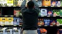 Miguel Bustillo stocks the beer cooler at a Walmart in Alexandria, Va. The world's largest retailer is focusing on adult beverages.