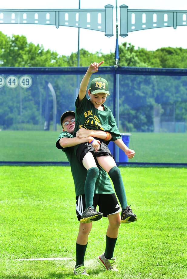 Luke Pliego, 11, lifts Mikey Pascento, 12, in a victory celebration, as their team, the Broadview Bombers beat the Danbury Bench Warmers 7 to 2, in the SLAMDiabetes Wiffle Ball Tournament in Danbury, Conn. Saturday, Aug. 10, 2013. Photo: Michael Duffy / The News-Times