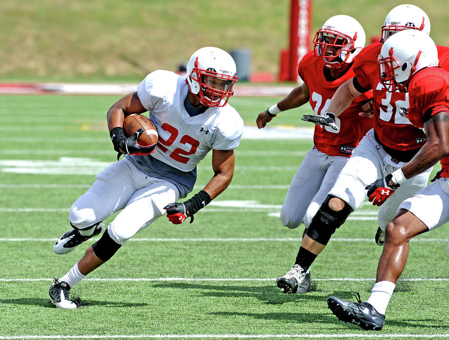 Running back Emmitt Raleigh,#22,  makes a run before being tackled by Xavier Bethany and Anthony Beard during the Lamar University football scrimmage on Saturday, August 10, 2013. Photo taken: Randy Edwards/The Enterprise Photo: Randy Edwards, Photojournalist / Enterprise