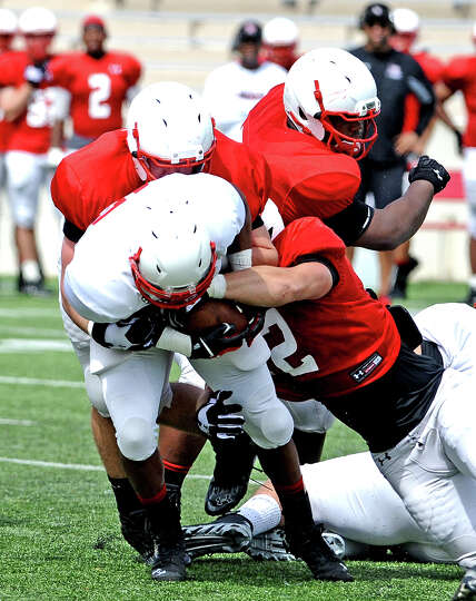 Cardinal lineman take down a running back during the Lamar University football scrimmage on Saturday