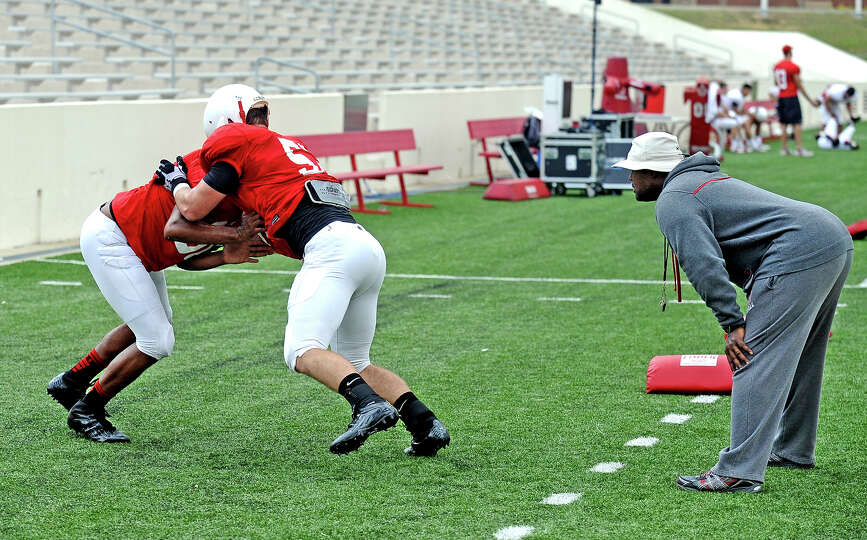 Cardinal football players go over drills before the Lamar University football scrimmage on Saturday,