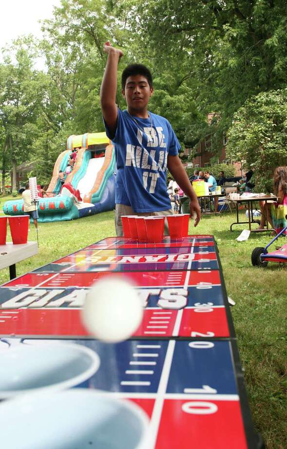 John Mendoza, 15, tries his hand at cup pong during the block party at Adams Garden Saturday, August 10, 2013. Photo: David Ames / Greenwich Time Freelance