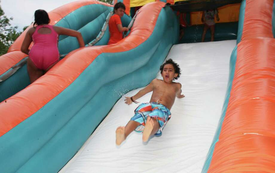 Sean Fatal, right, takes his turn on the water slide at the Adams Garden block party Saturday, August 10, 2013. Photo: David Ames / Greenwich Time Freelance
