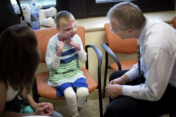 Dr. Jakub Tolar talks with 7-year-old Charlie Knuth, who has a rare genetic disease that causes his skin to slough off, in Minneapolis. Bone marrow transplants have helped to heal some of Knuth's lesions.