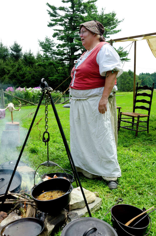 Volunteer Laurie Kommritz, of Bethel, dressed in Colonial clothing, teaches visitors how to cook over a fire at Historic Bradley-Hubbell House in Easton during the 5th annual Citizens for Easton Farm Tour on Saturday, Aug. 10, 2013. Photo: Amy Mortensen / Connecticut Post Freelance